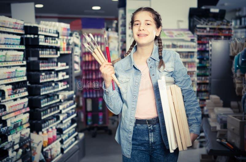 Rifornimenti teenager della tenuta della ragazza per la verniciatura in mani nel departme di arte fotografia stock