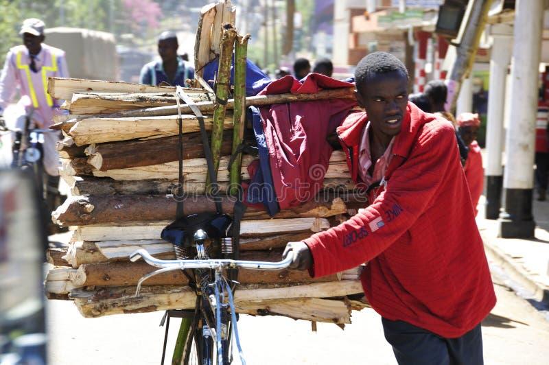 Rift Valley: Una madera que cuida del hombre joven en su canal del bycicle las calles de la ciudad de Eldoret imagen de archivo
