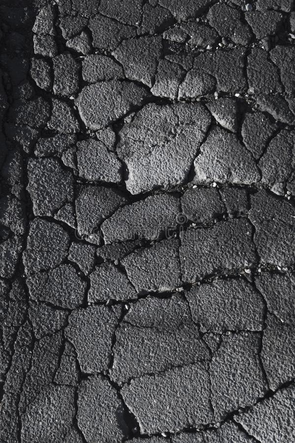 Rifts and cracks in a asphalt street road. Deep rifts and cracks on an old dark grey asphalt street road royalty free stock photography