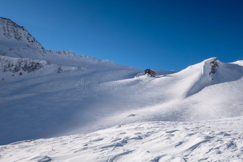 Rifugio alpino sotto la cresta della montagna nell'inverno su neve esposta al vento fotografia stock libera da diritti