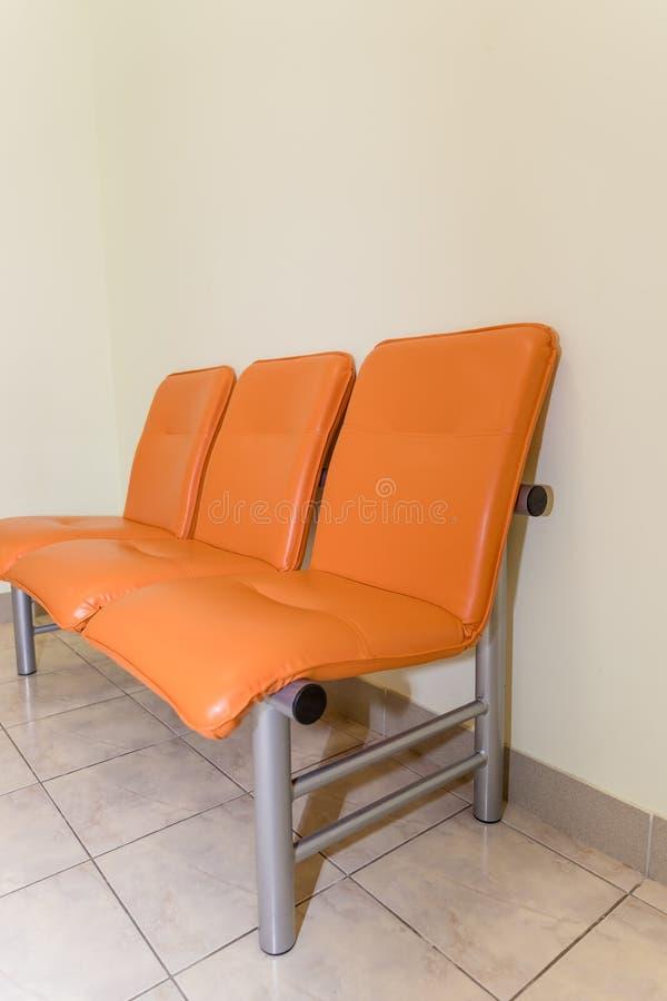 Rifugio dell'edificio pubblico Dettaglio interno dell'ospedale nessuno sedie arancio dell'ingresso dell'ospedale per aspettare de fotografie stock