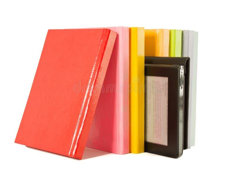 Riga dei libri variopinti e del lettore elettronico del libro fotografia stock