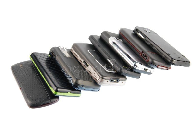Riga dei telefoni mobili moderni su bianco immagini stock
