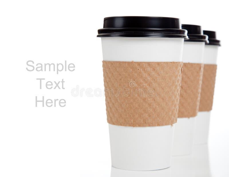 Riga delle tazze di caffè di carta su bianco con lo spazio della copia immagine stock