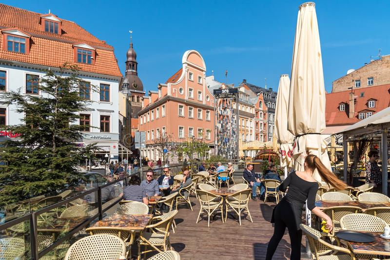 People relaxing and enjoying outdoor bar in the historic center of Riga, Latvia royalty free stock image