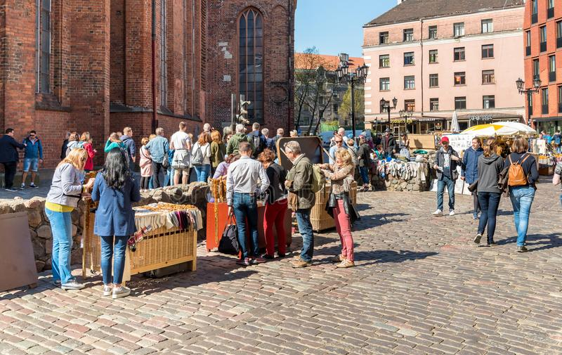 Tourists enjoying outdoor bars, shops and gift sellers in the historic center of Riga, Latvia royalty free stock image