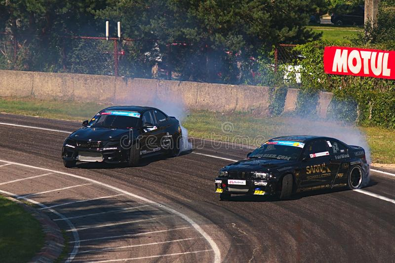 Riga, Latvia - August 02, 2019 - Two BMW drifting through first corners of the track stock images