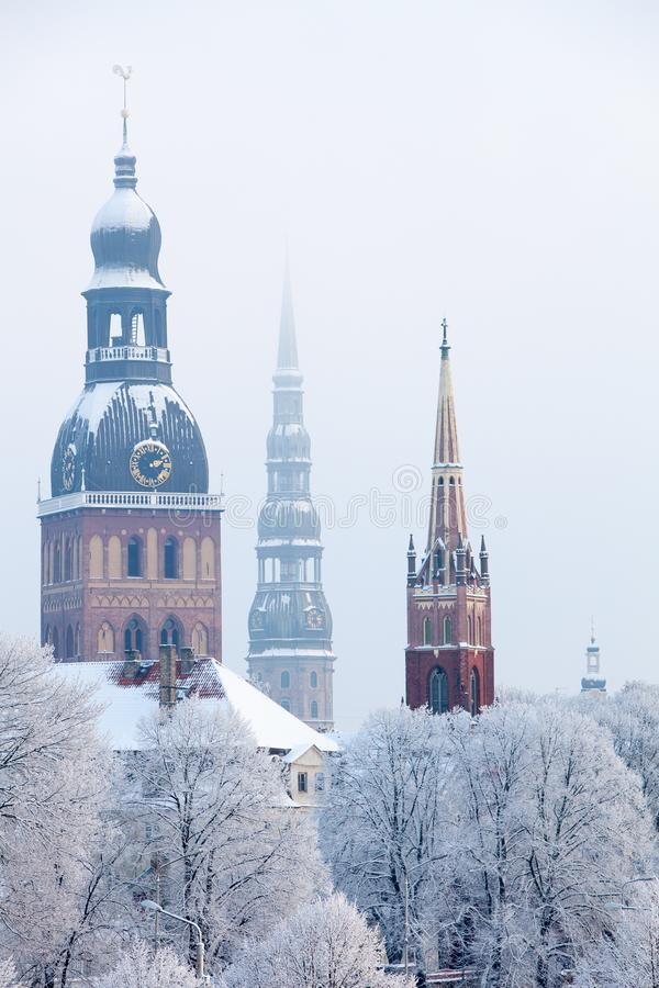 Riga, Latvia. Riga cityscape in winter. Several church towers, large park trees covered in hoarfrost royalty free stock image