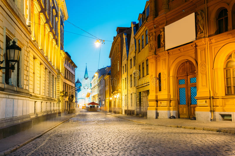 Riga Latvia. Evening View Of Deserted Pils Street, Ancient Architecture In Bright Warm Yellow Illumination stock images