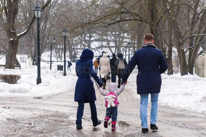 Family with small kid walking in park stock images