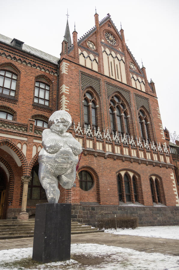 Riga, Latvia - January 1, 2016: The brick gothic building of Academy of Art in Riga, with woman statue from mirror pieces. stock photos