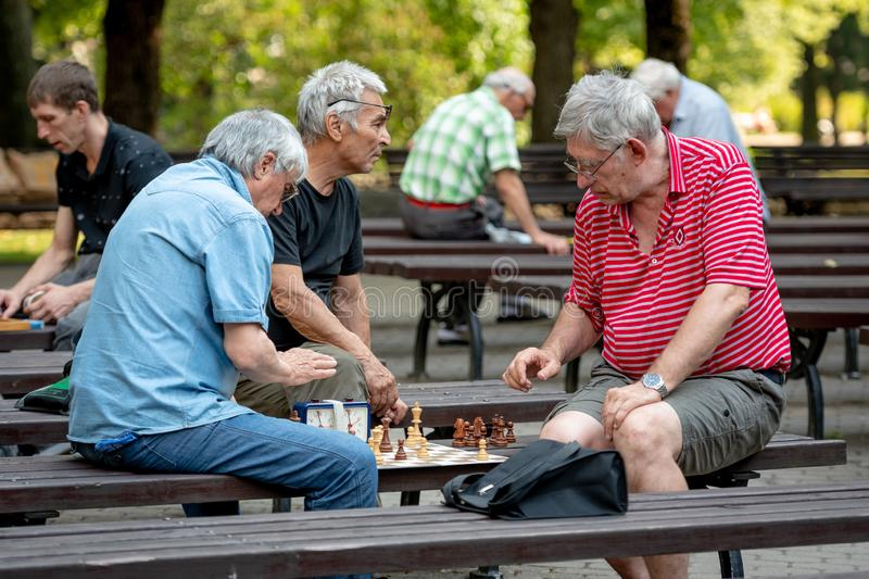 RIGA, LATVIA - JULY 18, 2018: Men seated on park benches and playing chess. royalty free stock image