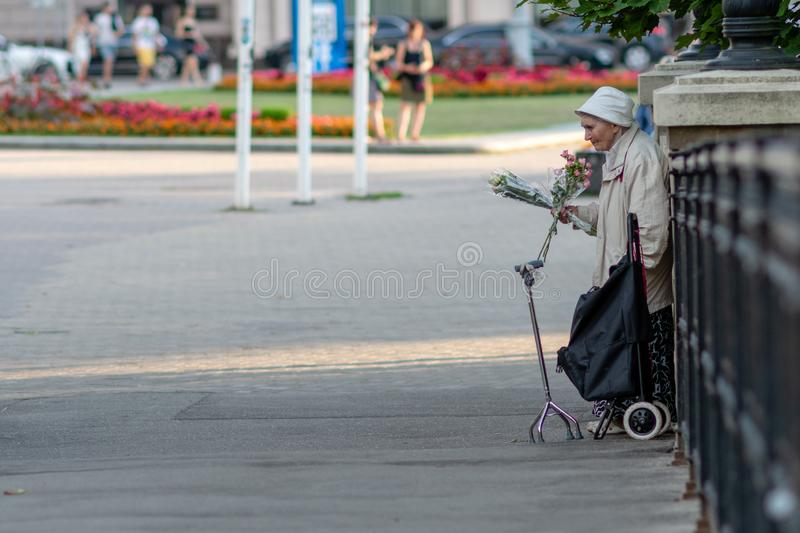 RIGA, LATVIA - JULY 26, 2018: An old woman standing at the bridge railing and selling flowers stock images