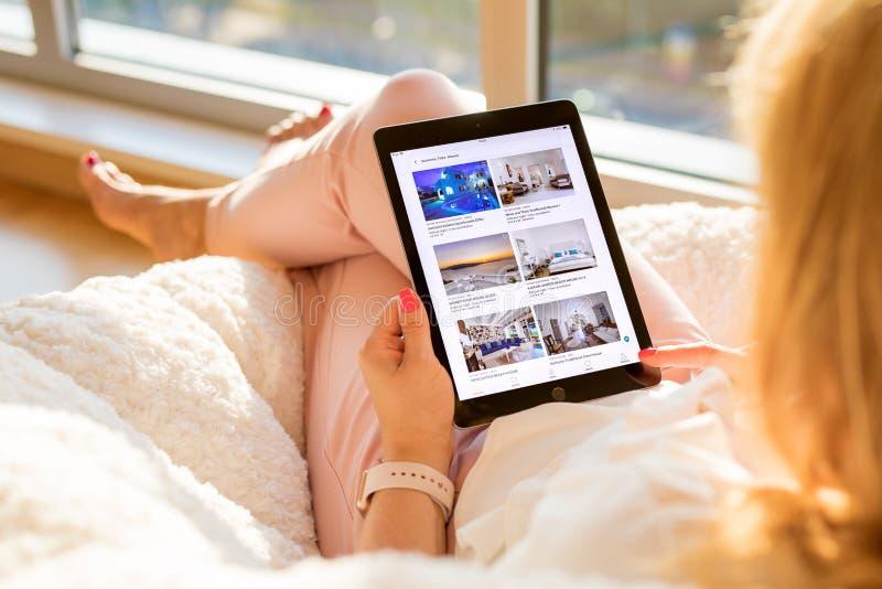 Riga, Latvia - July 21, 2018: Woman looking at Airbnb website on iPad. royalty free stock photos