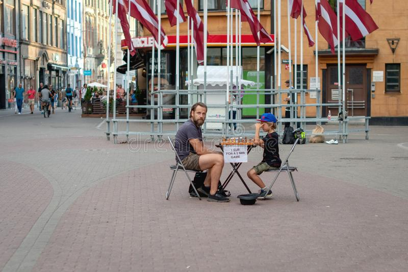 RIGA, LATVIA - JULY 26, 2018: A young boy on the street playing chess for money.  stock image