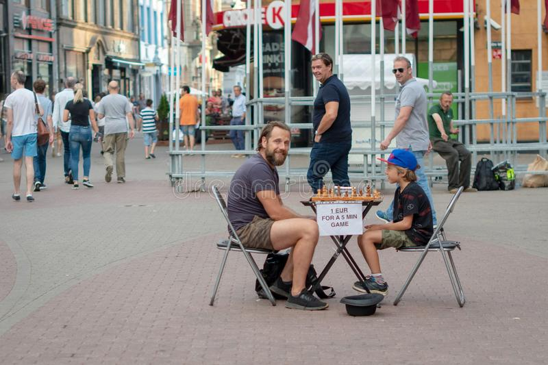 RIGA, LATVIA - JULY 26, 2018: A young boy on the street playing chess for money.  royalty free stock image
