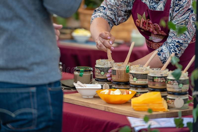 RIGA, LATVIA - JUNE 22, 2018: Summer solstice market. The seller. `s shoppers are offered to taste different nut butter royalty free stock images