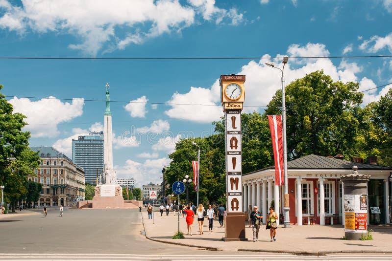 Riga, Latvia La gente que camina cerca de la señal local es reloj de Laima imagen de archivo libre de regalías