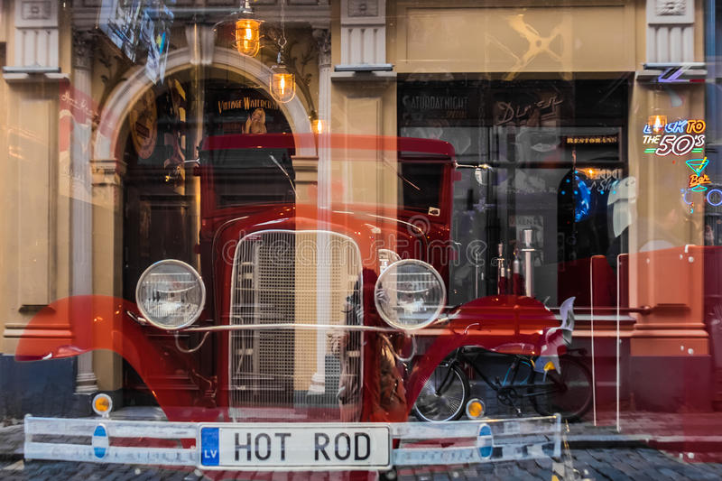 Riga, Latvia - March 20, 2017: Hot Rod in american vintage bar with photorgapher and street reflections. Selective focus. royalty free stock image