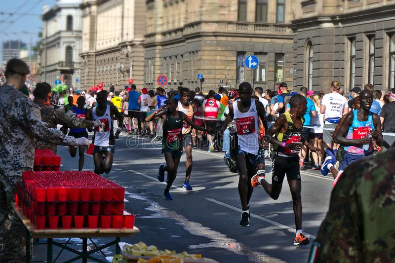 Riga, Latvia - May 19 2019: Elite male Runners passing refreshment point exhausted stock photos