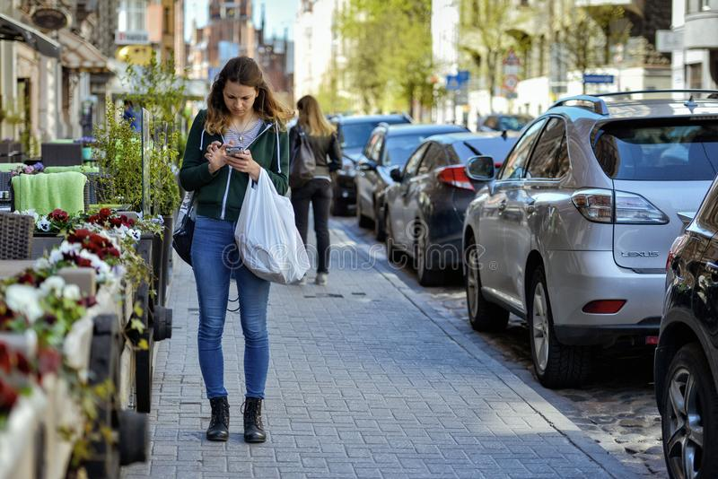 RIGA, LATVIA - MAY 12, 2017: A young woman stands on the sidewalk and reads a message on the phone. stock photos