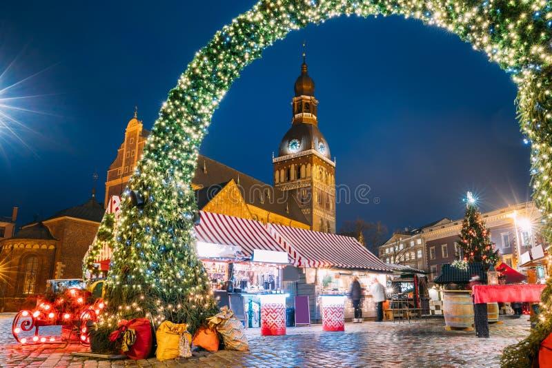 Riga, Latvia Mercado de la Navidad en cuadrado de la bóveda con la catedral de la bóveda de Riga Casas del árbol de navidad y de  imagen de archivo libre de regalías