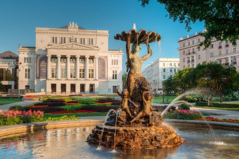 Riga, Latvia A ninfa da fonte na água espirra no bulevar de Aspazijas perto de Opera nacional imagem de stock royalty free