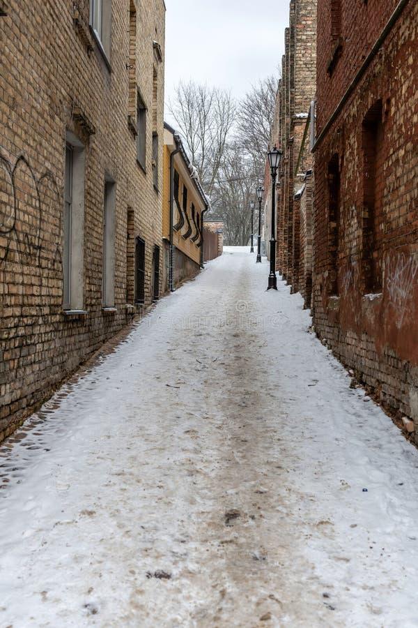 riga latvia Paisagem do inverno com o trajeto pedestre entre casas velhas do tijolo fotos de stock