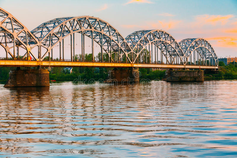 Riga, Latvia. Railway Bridge Through Daugava Or Western Dvina River. At Sunny Evening Sunset stock photos