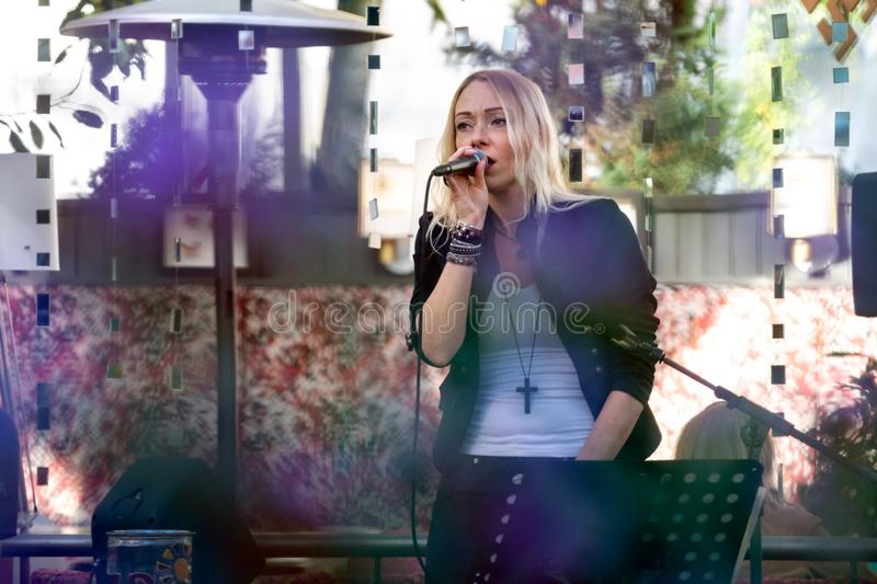 RIGA, LATVIA - SEPTEMBER 14, 2018: A blonde woman sings a karaoke outdoor cafe. stock image