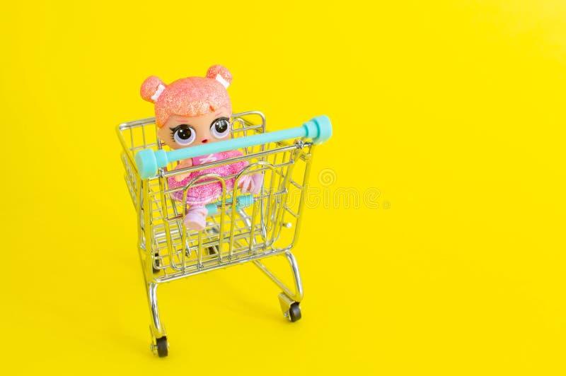 Riga, Letónia - 18 de abril de 2019: Boneca pequena que senta-se no mini trole de compra foto de stock