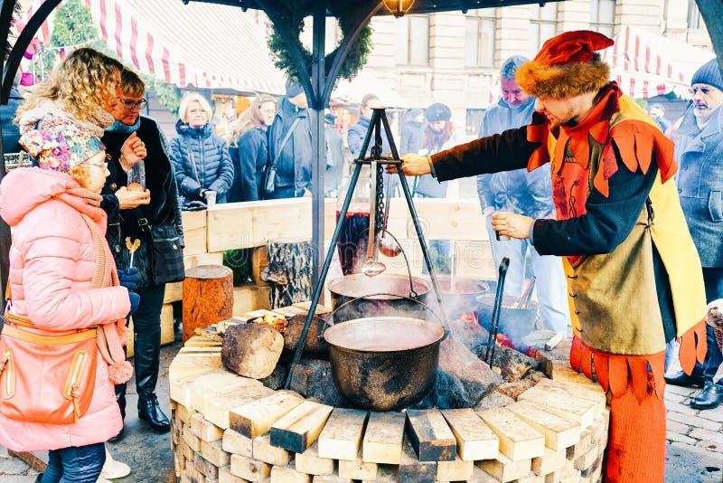 Riga, Letónia - 26 de dezembro de 2015: Os povos aleatórios apreciam uma refeição tradicional perto do potenciômetro enorme no me fotos de stock royalty free