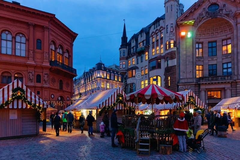 Riga, Letónia - 28 de dezembro de 2017: Povos no carrossel do Natal situado no quadrado da abóbada no mercado do Natal do inverno imagem de stock royalty free