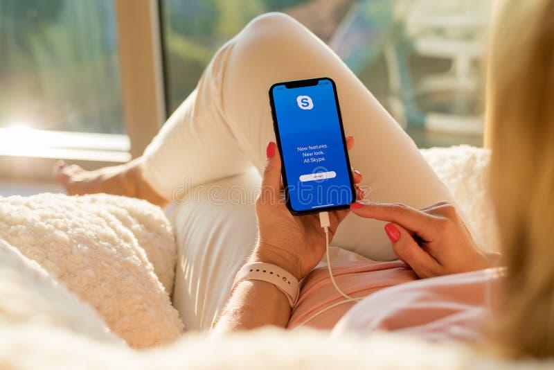 Riga, Letónia - 21 de julho de 2018: Mulher que usa o app de Skype no telefone celular foto de stock