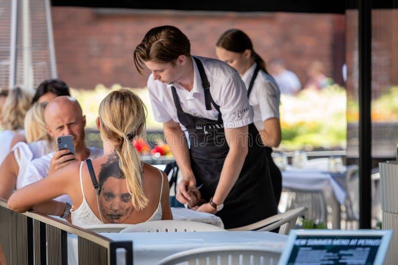 RIGA, LETÓNIA - 31 DE JULHO DE 2018: O café exterior na tabela senta uma mulher com uma grande tatuagem na sua para trás O empre fotografia de stock royalty free