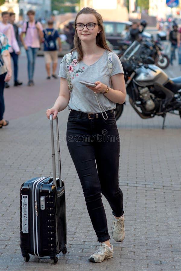 RIGA, LETÓNIA - 26 DE JULHO DE 2018: Uma jovem mulher com as malas de viagem nas rodas vai abaixo da rua fotos de stock royalty free