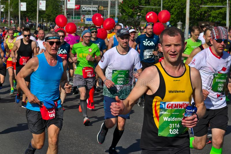 Riga, Let?nia - 19 de maio de 2019: Corredor de maratona masculino caucasiano que mostra os polegares acima foto de stock