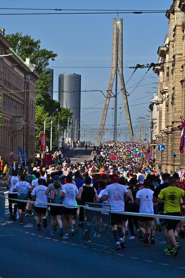 Riga, Let?nia - 19 de maio de 2019: Corredores de maratona que chegam ? ponte de Vansu fotos de stock