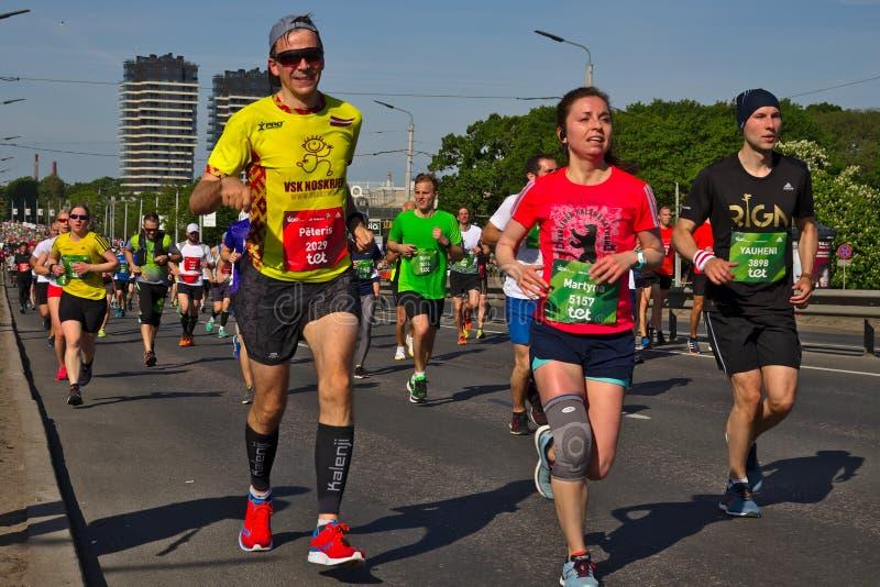 Riga, Let?nia - 19 de maio de 2019: Homem e corredores de maratona f?meas esgotados imagens de stock