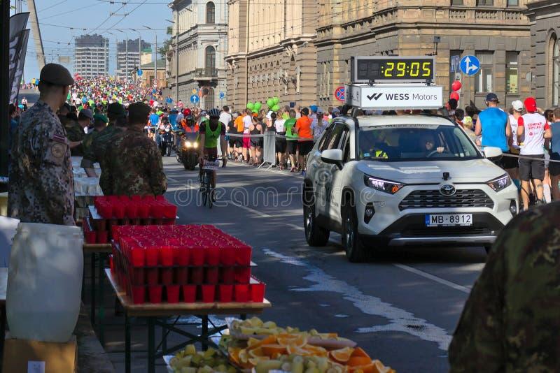 Riga, Let?nia - 19 de maio de 2019: Primeiros corredores da elite que aproximam a esta??o do rafrescamento atr?s do carro da pers imagem de stock royalty free