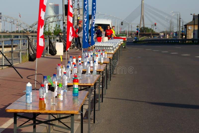 Riga, Let?nia - 19 de maio de 2019: Rafrescamentos preparados para os corredores de maratona ao lado da estrada vazia foto de stock royalty free