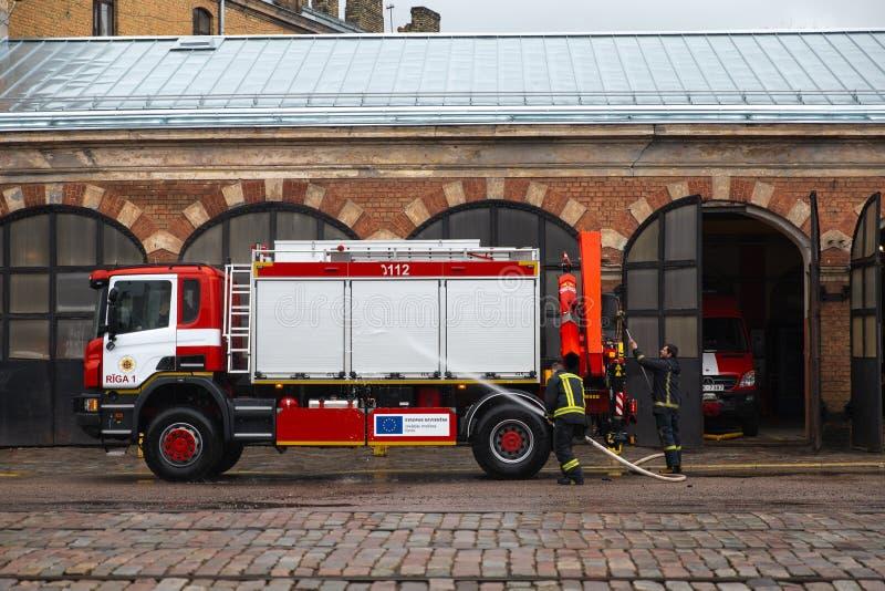 RIGA, LETÓNIA - 16 DE MARÇO DE 2019: O carro de bombeiros está sendo limpado - o motorista lava o caminhão do sapador-bombeiro em fotos de stock royalty free