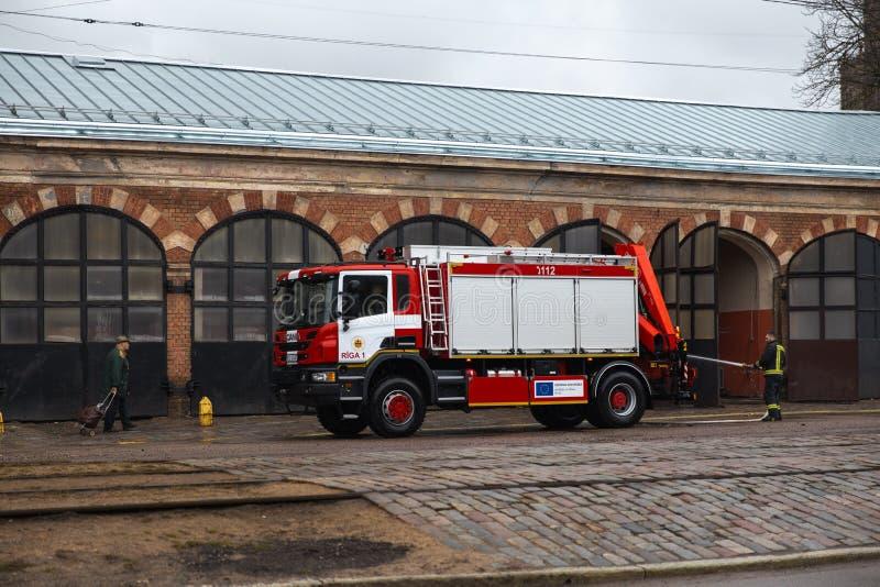 RIGA, LETÓNIA - 16 DE MARÇO DE 2019: O carro de bombeiros está sendo - o motorista lava o caminhão do sapador-bombeiro em um depo fotografia de stock royalty free