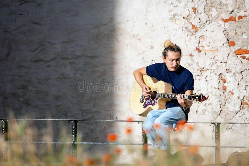 RIGA, LETÓNIA - 14 DE SETEMBRO DE 2018: O músico da rua senta-se em uma barreira do metal, joga-se a guitarra e canta-se foto de stock royalty free