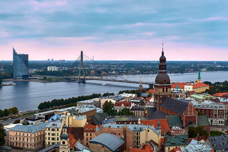 Riga, Letónia: opinião aérea do por do sol da cidade e do rio velhos do Daugava A torre da catedral da abóbada, um símbolo da cid imagens de stock royalty free