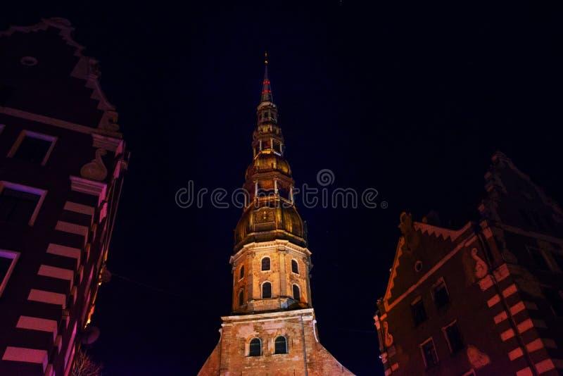Riga, Letónia: Opinião da noite da igreja de St Peter na cidade velha Riga Letónia Rua iluminada imagens de stock royalty free