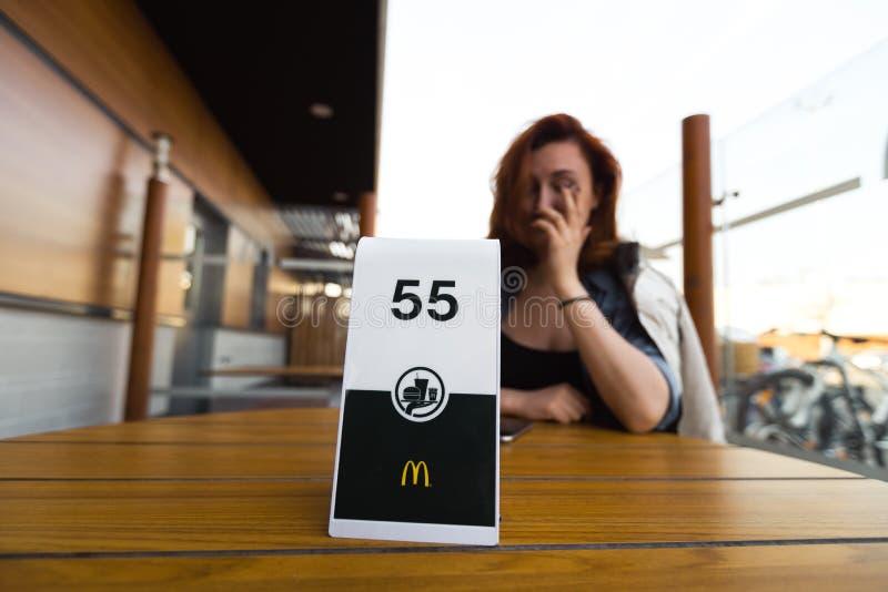 RIGA, LET?NIA - 22 DE ABRIL DE 2019: Ordem de espera e pensamento sobre seu peso - jovem mulher que come no fast food fotos de stock royalty free