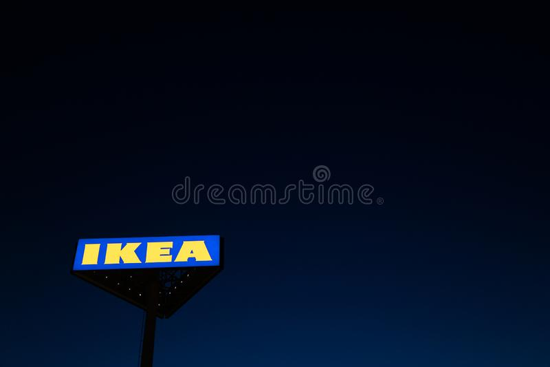 RIGA, LET?NIA - 3 DE ABRIL DE 2019: Sinal do tipo de IKEA durante a noite escura e vento - c?u azul no fundo imagem de stock royalty free