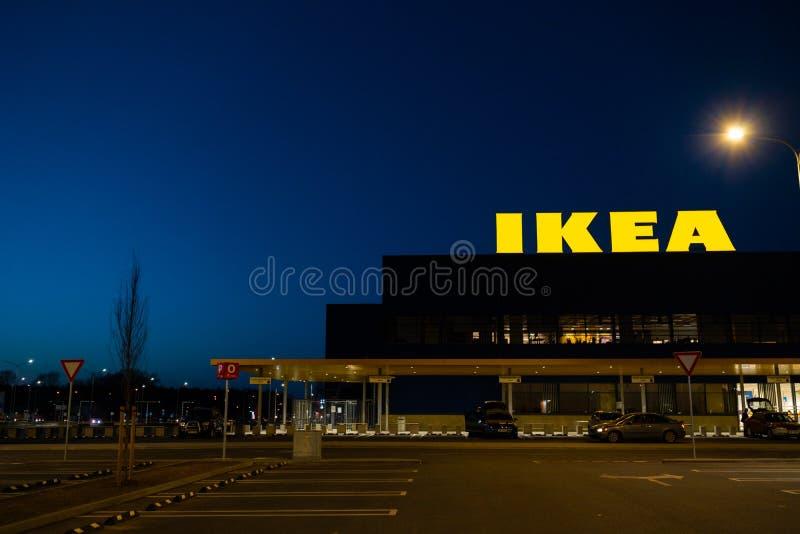 RIGA, LET?NIA - 3 DE ABRIL DE 2019: Sinal do tipo de IKEA durante a noite escura e vento - c?u azul no fundo imagens de stock royalty free