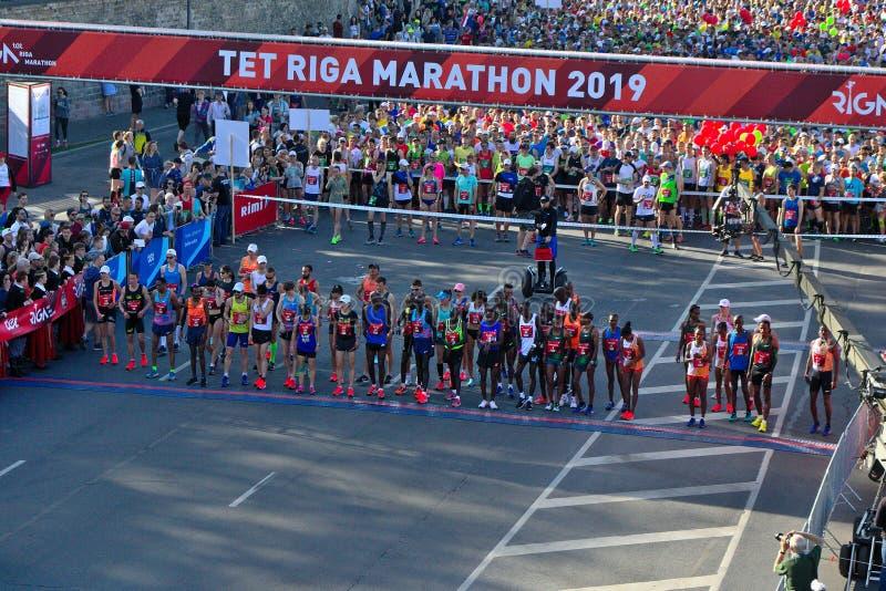 Riga, Let?nia - 19 de maio de 2019: Corredores da elite da maratona de Riga TET que enfileiram no in?cio a linha foto de stock
